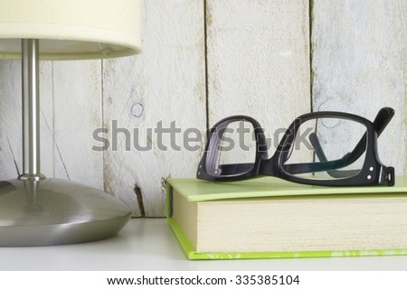 Shelf with glasses on a book and a lamp, ready for reading time. White wooden background. Empty copy space for editor's text.