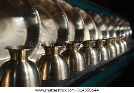 Shelf with kitchen utensils made of copper. Traditional decoration of the dining room in Asia. - stock photo