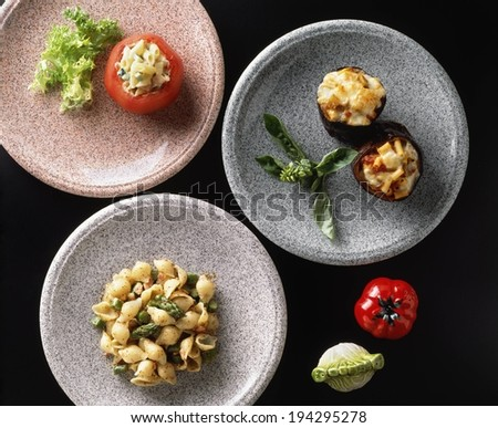 Shell pasta with asparagus served with two stuffed side dishes. - stock photo
