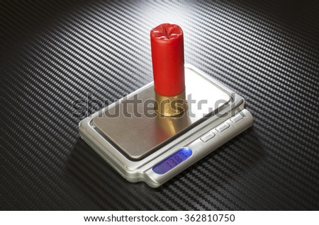 Shell that is used in a twelve gauge shotgun on a digital scale - stock photo