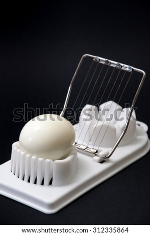Shelled boiled egg on a white chopper and black background. - stock photo