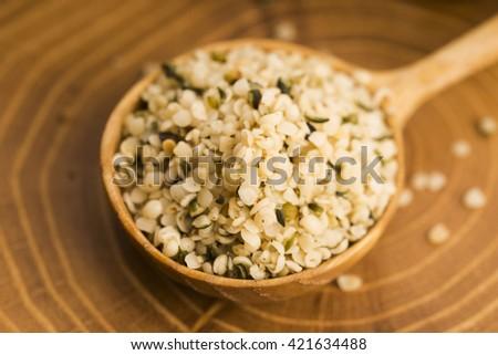Shelled hemp seeds on wood background - stock photo