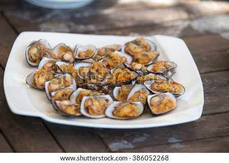 shellfish sea food in white plate on wood table