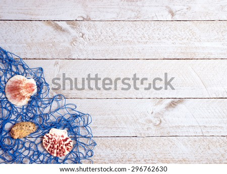 Shells and blue fishing net on wooden background with copyspace for individual text - stock photo