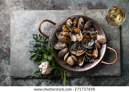 Shells vongole venus clams with parsley in copper cooking dish on stone slate background - stock photo
