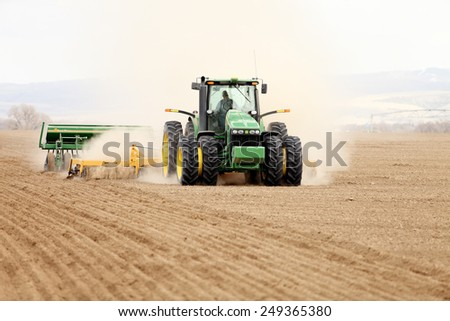 Shelly, Idaho, USA April 1 2013 A tractor working in the fields planting wheat. - stock photo