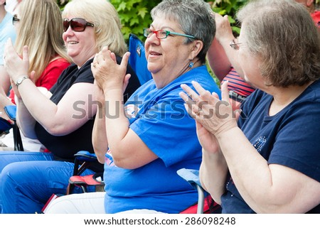 "Shelton, CT, USA - May 25, 2015: Spectators are enjoying the ""Veterans Day Parade"" held on May 25, 2015 in Shelton, Connecticut, USA"