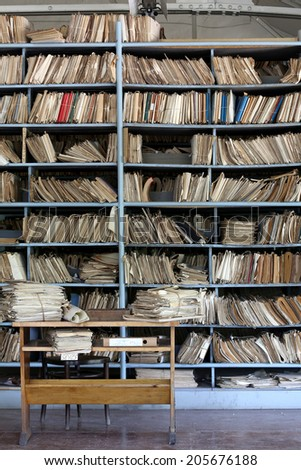 shelves full of files in a messy old-fashioned archive - stock photo