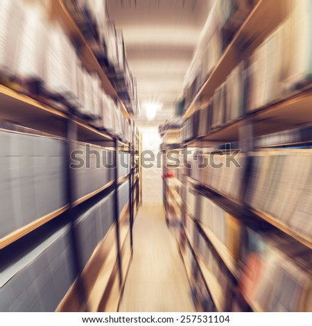Shelves full of paper documents stored in an old archive. Radial zoom effect defocusing filter applied, with vintage instagram look.  - stock photo