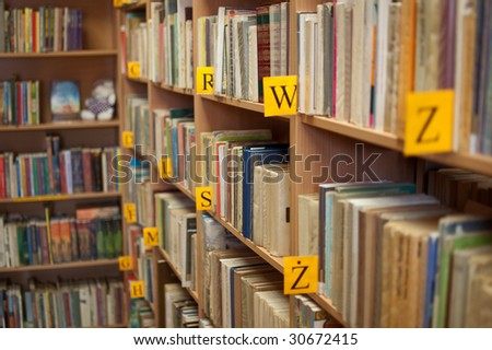 Shelves of books in library (shallow focus) - stock photo