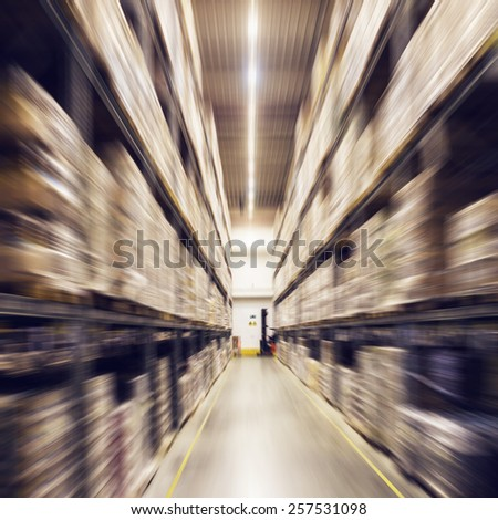 Shelves with boxes rows in a modern warehouse. Concept of trading, export, import or business. Radial zoom effect defocusing filter applied, with vintage instagram look.  - stock photo