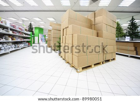 Shelves with variety of artificial Christmas tree and souvenirs inside large supermarket with boxes in center - stock photo