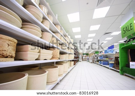 Shelves with variety of beige clay flowerpot inside large supermarket - stock photo