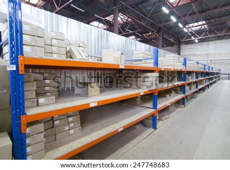 Shelving system with cardboard boxes in distribution warehouse.