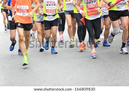 SHENZHEN, CHINA - DEC 08: Dozens of Unidentified athletes running at the shenzhen international marathon 2013, shennan road,shenzhen city,China,on DEC 08,2013 at Shenzhen city,Guangdong province,China.  - stock photo