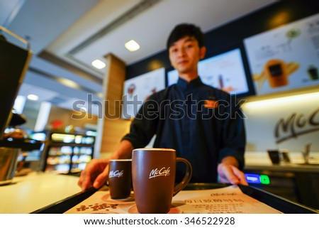 SHENZHEN, CHINA - OCTOBER 22, 2015: cup with hot coffee on the tray in McCafe's. McCafe is a coffee house style food and drink chain, owned by McDonald's. - stock photo