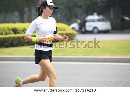 SHENZHEN - DEC 08: Unidentified athlete(number12422)running at the shenzhen international marathon 2013, shennan road,shenzhen city,China,on DEC 08,2013 at Shenzhen city,Guangdong province,China.  - stock photo