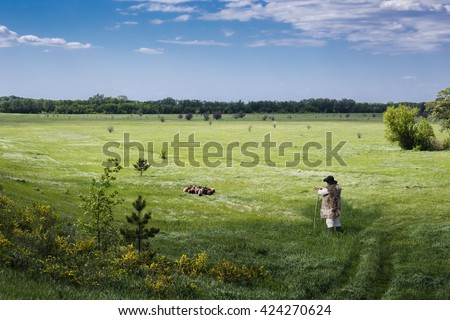 Shepherd and flock of sheep on a green pasture
