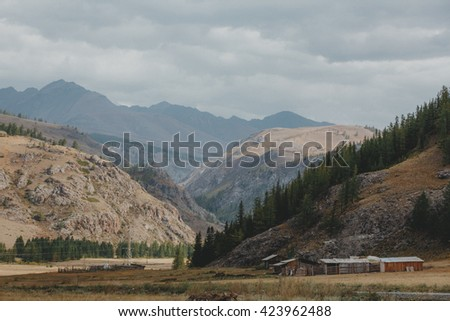 Shepherd's house in a spring landscape in the mountain. Foggy morning in the Altay mountains. - stock photo