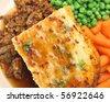Shepherd's pie with peas, carrots and gravy. - stock photo