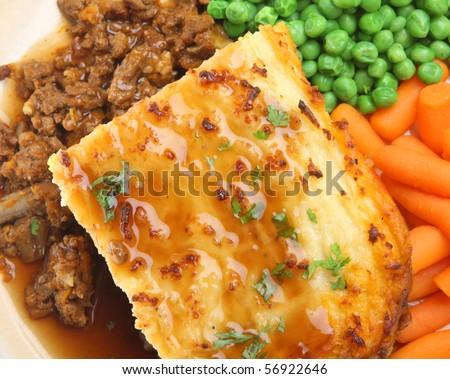 Shepherd's pie with peas, carrots and gravy. - stock photo