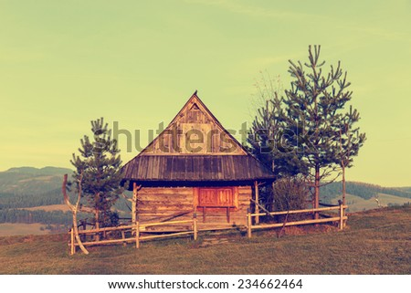 Shepherd wooden hut on meadow in autumn season, vintage look - stock photo