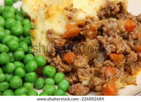 Shepherds pie served with peas. - stock photo