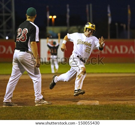 SHERBROOKE, CANADA - August 7: Manitoba's Chad Millar rounds third base against New Brunswick in men's baseball at the Canada Games August 7, 2013 in Sherbrooke, Canada. - stock photo