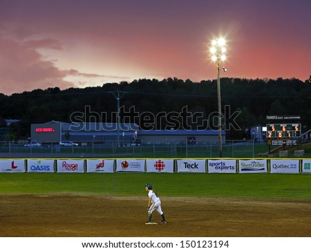 SHERBROOKE, CANADA - August 4: The sun sets on a women's softball game at the Canada Games August 4, 2013 in Sherbrooke, Canada. - stock photo