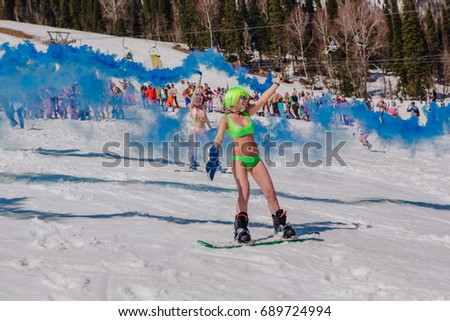 Sheregesh, Kemerovo region, Russia - April 22, 2017: Grelka Fest is a sports and entertainment activity for ski and snowboard riders in bikini. Group of young women on a snowboard in colorful bikini.