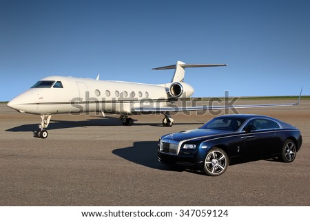 SHEREMETYEVO, MOSCOW REGION, RUSSIA - APRIL 24, 2015: Private Gulfstream G550 executive airplane with Rolls Royce Wraith luxury car shown together at Sheremetyevo international airport. - stock photo