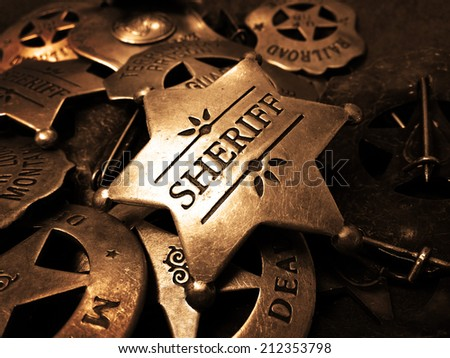 Sheriff's tin badge in pile of star law enforcement badges - stock photo