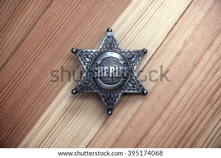 sheriff star on wood table closeup - stock photo