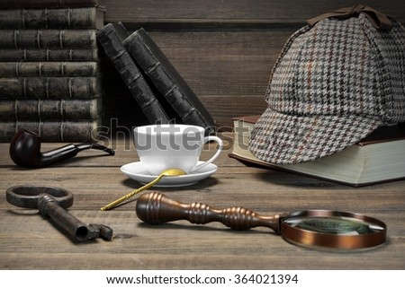 Sherlock Concept. Private Detective Tools On The Wood Table Background. Deerstalker Cap,  Magnifier, Key, Cup, Notebook, Smoking Pipe. Front View - stock photo