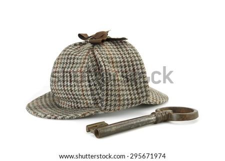 Sherlock Holmes Deerstalker Cap And Old Vintage Big Key Isolated On White Background. Investigation Or Solve Crimes Concept - stock photo