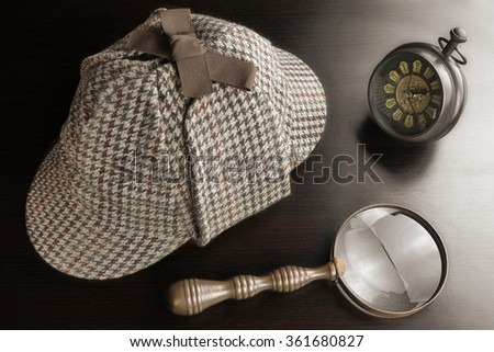 Sherlock Holmes Deerstalker Hat And Vintage Clock And   Magnifying Glass On The Black Wooden Table Background. Overhead View.  Investigation Concept.