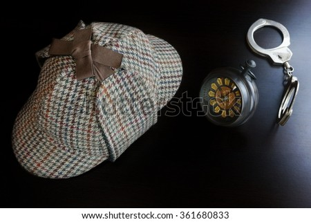 Sherlock Holmes Deerstalker Hat, Hand Cuffs, Vintage Retro Clock On The Black Wooden Table Background In The Back Light