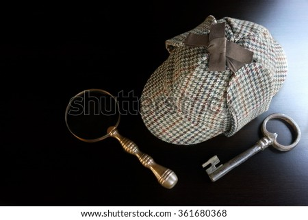 Sherlock Holmes Deerstalker Hat, Old Key And Vintage  Magnifying Glass On The Black Wooden Table Background. Overhead View.  Investigation Concept. - stock photo