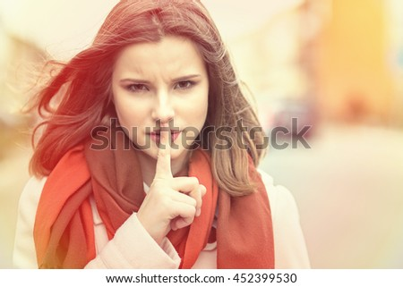 Shh Woman wide eyed asking for silence or secrecy with finger on lips hush hand gesture cityscape outdoor background Pretty girl placing fingers on lips sign symbol. Negative emotion facial expression - stock photo