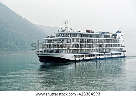 SHIBAOZHAI, CHINA â?? April 15, 2016: Chinese river cruiser on the Yangtze River in a hazy morning. Chinaâ??s cruise ship industry is expected to expand to 4.5 million passengers a year by 2020.