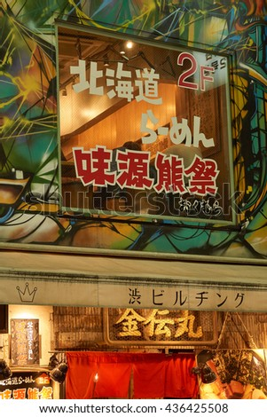 SHIBUYA, TOKYO, JAPAN - AUGUST 2015: Isolated modern shop facade at night in the busy streets of downtown Shibuya.