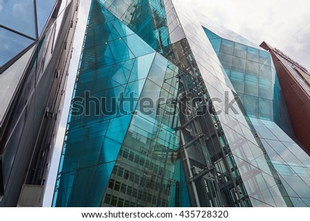 SHIBUYA, TOKYO, JAPAN - AUGUST 2015: Modern architecture in Tokyo, the amazing Audi Forum building, with asymmetric reflecting glass facade, also called Iceberg. - stock photo