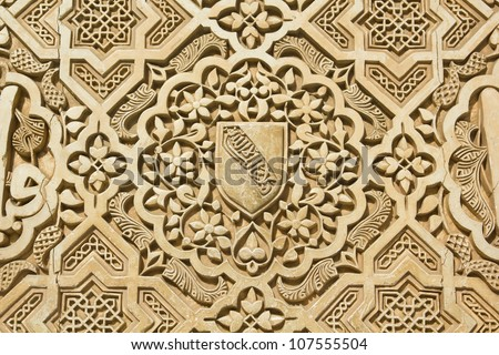Shield of the Nazari kingdom of Granada.  Arabic stone engravings on the Alhambra palace wall in Granada, Spain - stock photo