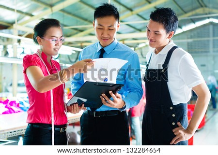 Shift supervisor or foreman, together with the owner or CEO and the designer, look at a draft for the new collection, they standing in a textile factory - stock photo