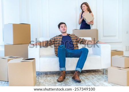 Shifting a family. Love couple sitting on the couch and show a thumbs up while young and beautiful couple in love sitting in an empty apartment among boxes - stock photo
