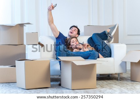 Shifting to a new life. A girl and a guy holding boxes for moving the hands and smiling at the phone camera while a couple in love making selfie at the window among boxes - stock photo