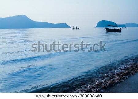 shillouette boats in the large blue sea