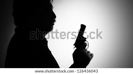 shiluette of man with a revolver, black white