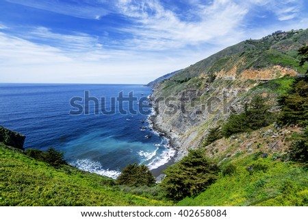 Shimmering aquamarine sea, blue skies, white clouds & gentle waves splashing along the rugged Big Sur coastline, viewed from jagged cliffs of Ragged Point by Highway 1 on the California Central Coast.