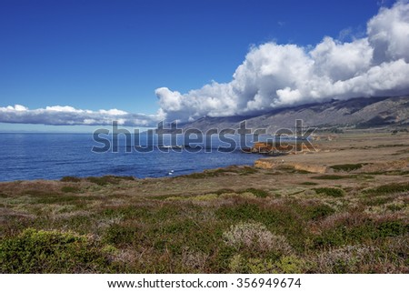 Shimmering reflective sunlight, blue skies, white clouds and waves splashing along the rugged Big Sur coastline, viewed from jagged cliffs of Ragged Point by Highway 1 on the California Central Coast. - stock photo